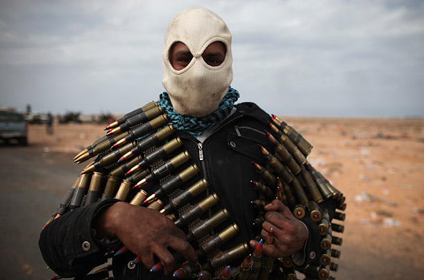 A Libyan volunteer carries ammunition on the outskirts of the eastern town of Ras Lanouf.