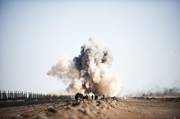 Smoke rises after a Libyan fighter jet drops a bomb on rebel soldiers on the outskirts of Ras Lanuf.