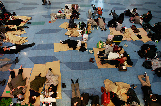 Travelers rest on a floor at the Haneda International airport in Tokyo, after the massive earthquake in Japan.