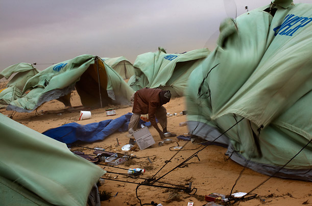 A Somalian man collects his belongings, which were spread out during a sandstorm at a refugee camp on the Tunisia-Libya border.