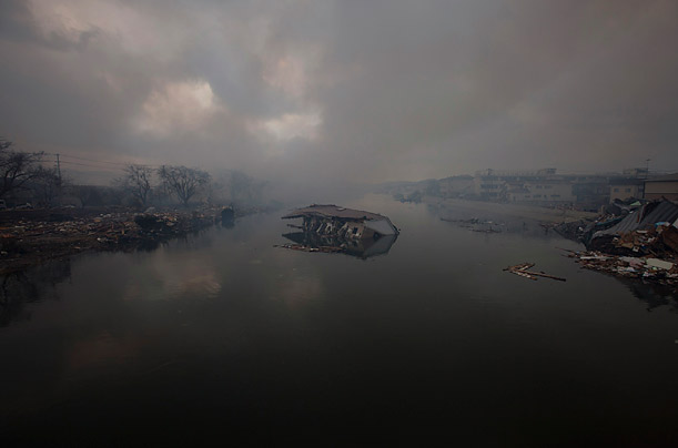 A damaged house floats in a river in Kesennuma, Japan, days after the area was devestated by an earthquake and tsunami.