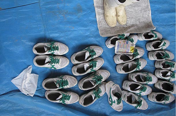 Shoes left by people evacuated from areas affected by the Japanese earthquake lie at the entrance of a shelter in Ostuchi. 