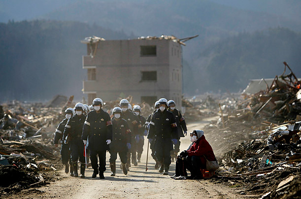 Emergency workers walk past survivors sitting near debris in Rikuzentakata, Iwate prefecture, where the earthquake and tsunami hit last week.