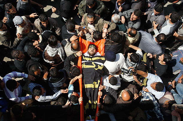 The body of an Islamic Jihad militant, who was killed during Israeli air strikes, is lifted up by mourners during his funeral in Gaza City.