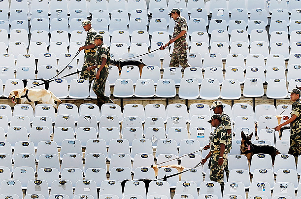 Security personnel search the Punjab Cricket Association Stadium stadium with sniffer dogs before the 2011 ICC World Cup second Semi-Final in Mohali, Indi