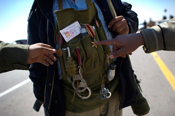 A Libyan rebel points to the medal of a comrade near Brega.