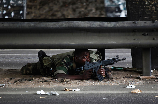 A soldier loyal to Ivory Coast presidential claimant Alassane Ouattara lies on a road as fighting flares in Abidjan, Ivory Coast.