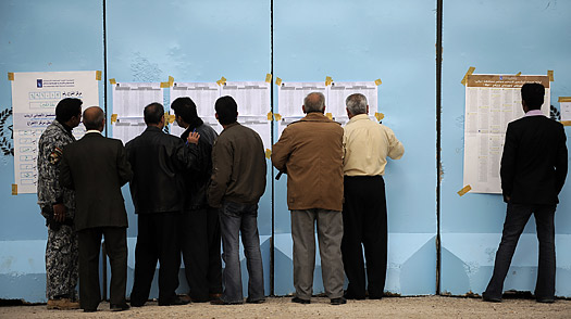 Iraqi men look at the electoral lists at the entrance of a polling station in the eastern town of Khanaqin, in Diyala province near Iraq's border with Iran, on January 31, 2009.