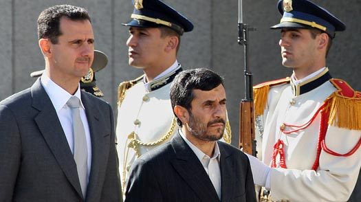Syrian President Bashar al-Assad (R) and his Iranian counterpart Mahmoud Ahmadinejad review an honor guard at Al-Shaab presidential palace in Damascus, Syria on the eve of Obamas announcement that he was renewing sanctions. Mitchell is headed for Damascus so forward momentum is being maintained. Louai Beshara / AFP / Getty