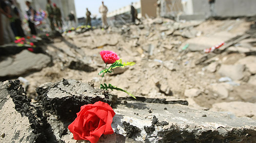Plastic flowers are placed along the rim of the blast crater by relatives and friends of victims of the bomb site outside the Foreign Affairs Ministry building in central Baghdad.