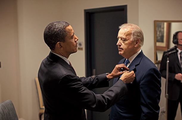 The President adjusts the Vice President's flag pin before being introduced at the White House job summit in early December.