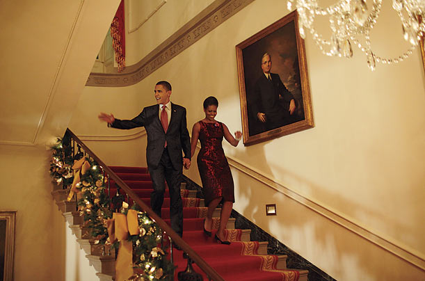 The First Couple greets guests at a White House holiday party on December 3.