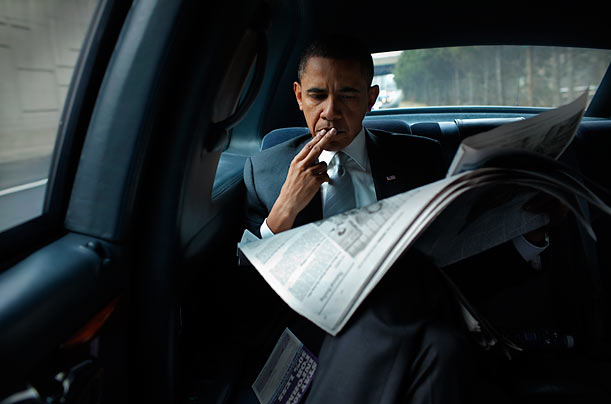 president obama one year in photo essays time keeping current president obama reads the paper in the presidential state car on his way back
